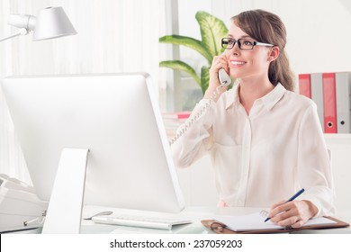 Pretty secretary talking on telephone and making notes