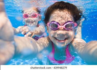 Pretty selfie  two little girls under the water.