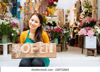 Pretty seller of the shop sitting with Open sign