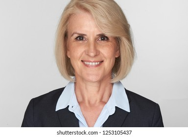 Pretty senior business woman is smiling toothy wearing suit. Cheerful beautiful old lady isolated on grey