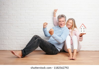 pretty senior couple sitting on their house floor. family or home concept