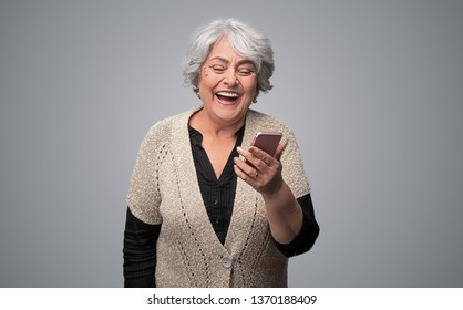 Pretty senior female in elegant outfit using modern smartphone and laughing out loud while standing on gray background. Old woman watching funny videos on internet