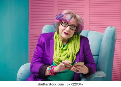 Pretty senior woman holding golden smart phone and sitting in blue armchair, wearing glasses. Concept of bright informal aged businesswomen