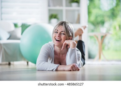 a pretty senior woman at home , she is lying on her stomach on floor. she practices pilate. she is smiling. the focus is on her and the background is blur. there is a big green ball behind her
