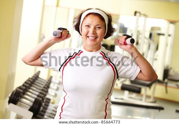 Pretty senior woman pumping muscles