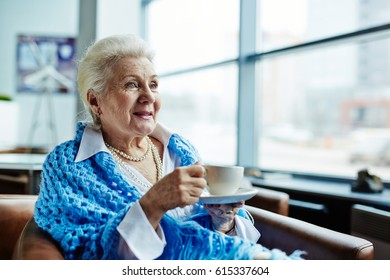 Pretty senior woman relaxing in cozy armchair and warming herself with cup of hot tea after long walk through winter city