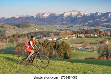 pretty senior woman riding her electric mountain bike in early springtime in the Allgau mountains near Oberstaufen, in warm evening light below the spectacular snow capped mountains of Nagelfluh chain