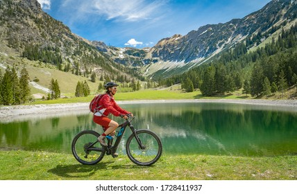 pretty senior woman riding her electric mountain bike at the Seealp lake in the Nebelhorn area above  Oberstdorf, Allgau Alps, Bavaria, Germany