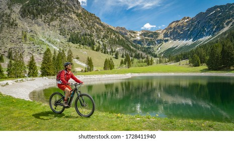 pretty senior woman riding her electric mountain bike on the Wallraff Trail in the Nebelhorn area above  Oberstdorf, Allgau Alps, Bavaria,
