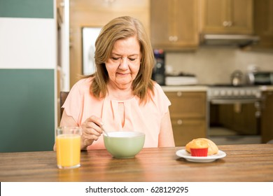 Pretty senior woman sitting in the kitchen and without appetite for breakfast