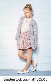 Pretty seven year old girl stands by a white brick wall and smiling. Kid's fashion. Spring style.