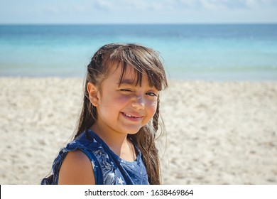 Pretty seven year old hispanic girl squinting eyes due to the sun light on the beach.