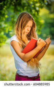 Pretty severe young girl reads red book, against green of summer park.
