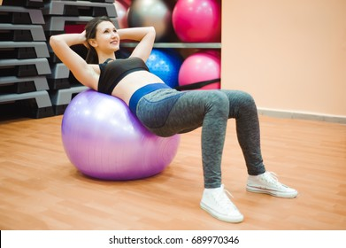 Pretty sexual straight fitness woman with musculat body lying on big ball in sport hall training indoor, horizontal picture