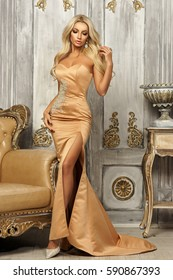 Pretty sexy blonde woman wearing long evening slit gown or dress and standing in luxury gray colors interior with yellow armchair.