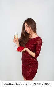 Pretty sexy brunette woman on white background. Beautiful young lady in beige glitter sequins evening dress looking over shoulder holding glass of champagne and gift in hand