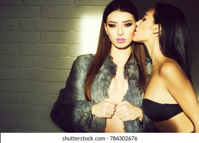 Pretty sexy cute woman in gray fur with fashion makeup and girl in black bra kissing on brick wall background, copy space