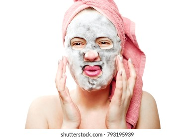 Pretty sexy girl with face mask, oxygen mask for face, happy girl looks after the skin of the face, close-up portrait emotional girl with a pink towel on her head on a white background isolated