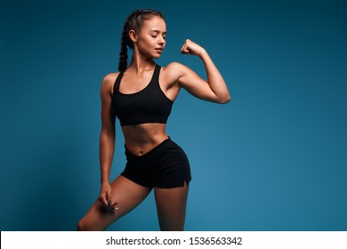 pretty sexy slim attractive girl in fashion bra and shorts shows her biceps. close up photo. isolated blue background, studio shot. copy space. strength training, health and body care