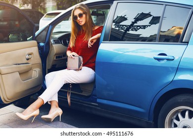 Pretty  sexy stylish  woman in car. Successful young lady  posing on street , sitting in her vehicle. Wearing stylish  fall outfit, sunglasses, white  trousers and elegant handbag.