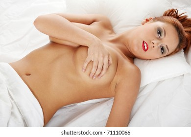 Pretty sexy topless woman on the bed.