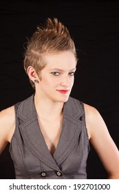 Pretty, short haired woman in a grey vest,   looking at the camera with a friendly and  thoughtful expression