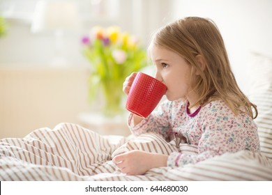 Pretty sick little child girl laying in bed and drink tea