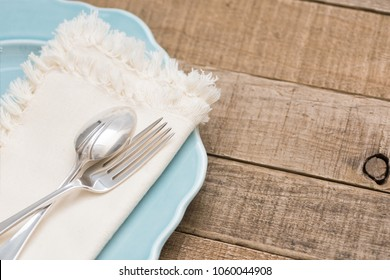 Pretty and Simple arrangement of a Table Place Setting with Fork, Spoon, White Napkin on a Teal Plate on Rustic Wood Board Background with room or space for copy, text, your words.   Horizontal