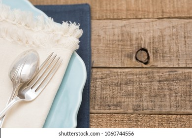 Pretty and Simple arrangement of a Table Place Setting with Fork, Spoon, White Napkin on a Teal Plate on Rustic Wood Board Background with room or space for copy, text, your words.