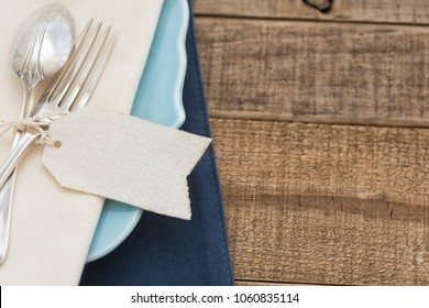 Pretty and Simple arrangement of a Table Place Setting with Fork, Spoon, White Napkin and blank name tag on a Teal Plate on Rustic Wood Board Background with room or space for copy, text, your words.
