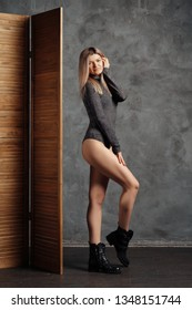 Pretty size plus model posing near folding screen over grunge abstract wall on background in closed body and rough boots