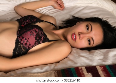 Pretty slender Chinese woman in a pink and black bra and jeans