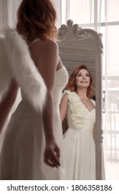 Pretty, slender woman with wings. Female in stage image of an angel. Emotions of girl in dress standing at mirror in an old textured interior room. Actress shows her abilities. Author space in photo