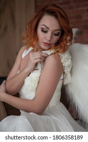 Pretty, slender woman with wings. Female in stage image of an angel. Emotions of girl in dress sitting on chair in an old textured interior room. Actress shows her abilities. Author space in photo