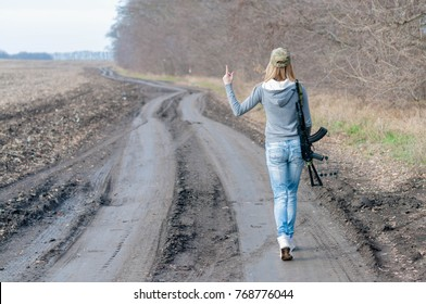 Pretty slim blond girl in a camouflage cap with big black gun on her shoulder walking along dirty car track with mud and puddles near forest in cold autumn day and show her thumbs up