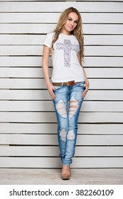 Pretty slim blonde in jeans and t-shirt posing near the white wooden wall