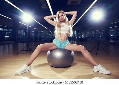Pretty slim blonde woman with long hair, dressed in white crop top, blue shorts and trainers, sitting on silver exercise ball spreading legs wide apart against two bright lights and gym on background.