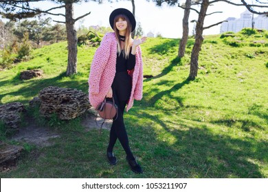 Pretty slim stylish brunette woman walking  in sunny spring park. Wearing black shoes. fluffy pink cardigan and elegant casual hat .