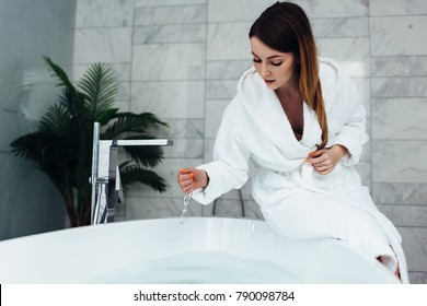 Pretty slim woman wearing bathrobe sitting on edge of bathtub filling up with water