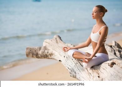 Pretty slim Woman in white costume doing Yoga pose near big tree