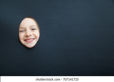 Pretty small girl with cartoon plaits against the black background. Photo face stand-in cutout