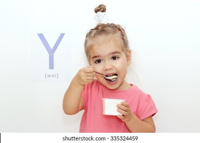 Pretty small girl eating a yogurt over white background with Y letter on it, indoor portrait
