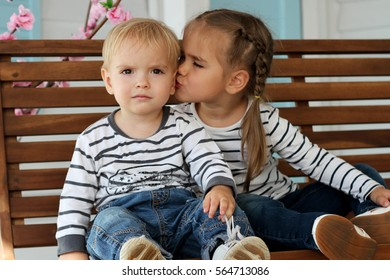 Pretty small girl and her brother in jeans and jogging white shoes sitting on the wooden bench, girl kisses her brother, beauty and fashion concept, indoor portrait, focus on the boy