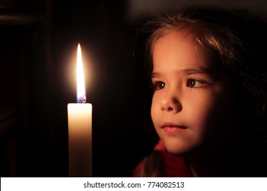 Pretty small girl is looking on the light of candle over dark background, old folk-belief for young women to see their future, religion and folklore concept, close-up portrait