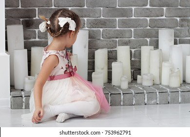 Pretty small real lady sitting before white decorative fireplace with candles, winter holiday concept, happy family, lifestyle indoor, studio shot