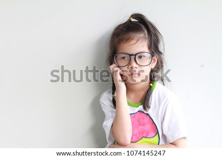 6b8adeb522 Pretty smart 5 years old Asian girl with pigtails wearing glasses.Thinking  of something.