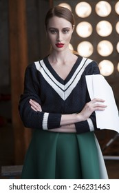 Pretty smart actress wearing sweater holding her scripts. Cross arms.