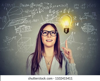 Pretty smart brunette in glasses pointing up in enlightenment of solution and creative idea