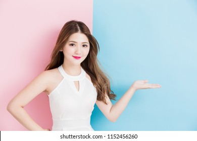 pretty smile girl standing with arms akimbo and showing isolated on a pink and blue background.