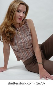 Pretty smile on this model wearing copper outfit posing in the studio